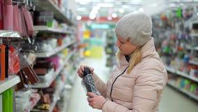 Μια μέσης ηλικίας γυναίκα σε ένα καπέλο και ένα κάτω σακάκι επιλέγει τα μαύρα thermos σε μια υπεραγορά φιλμ μικρού μήκους