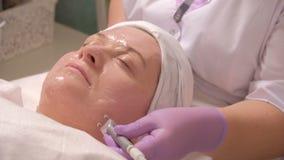 Μια μέσης ηλικίας γυναίκα στη διαδικασία σε ένα σαλόνι ομορφιάς Ανύψωση, τόνος δερμάτων Ένα επαγγελματικό cosmetologist λειαίνει  απόθεμα βίντεο