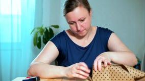 Μια μέσης ηλικίας γυναίκα συσκευάζει ένα δώρο απόθεμα βίντεο