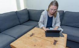 Μια μέση ηλικίας γυναίκα που χρησιμοποιεί στο σπίτι το φορητό προσωπικό υπολογιστή της Στοκ φωτογραφία με δικαίωμα ελεύθερης χρήσης