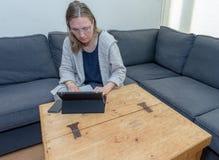 Μια μέση ηλικίας γυναίκα που χρησιμοποιεί στο σπίτι το φορητό προσωπικό υπολογιστή της Στοκ Φωτογραφίες