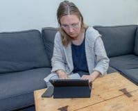 Μια μέση ηλικίας γυναίκα που χρησιμοποιεί στο σπίτι το φορητό προσωπικό υπολογιστή της Στοκ Εικόνες