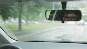 Μια μέση ηλικίας γυναίκα στα γυαλιά κάθεται στο τιμόνι ενός αυτοκινήτου φιλμ μικρού μήκους
