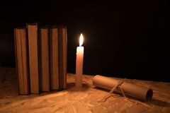 Μια μαγική σφαίρα, ένας κύλινδρος, ένα κερί και ένα παλαιό βιβλίο στο σκοτάδι της νύχτας Στοκ Εικόνες