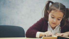 Μια μαθήτρια κάθεται στον πίνακα Διαβάζοντας αυτό το βιβλίο, διαβάζει r φιλμ μικρού μήκους