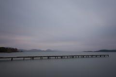 Μια μακριά αποβάθρα σε μια λίμνη στο σούρουπο, με τέλεια ακόμα το νερό και το MO Στοκ Φωτογραφία