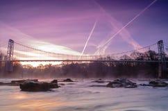Μια μακροχρόνια άποψη έκθεσης της γέφυρας αναστολής Dinckley στην ανατολή που διασχίζει τον ποταμό Ribble κοντά σε Hurst πράσινο  στοκ εικόνες