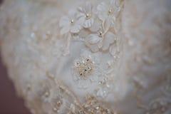 Μια μακρο φωτογραφία ενός λεπτομερούς άσπρου γαμήλιου φορέματος με τα άσπρα λουλούδια και τα πλαστά διαμάντια έπλεξε στο φόρεμα Στοκ Εικόνες