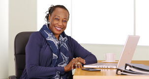 Μια μαύρη επιχειρηματίας θέτει για ένα πορτρέτο στο γραφείο της στοκ εικόνες