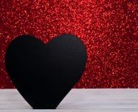 Μια μαύρη καρδιά με ένα λαμπρό κόκκινο υπόβαθρο Στοκ Εικόνες