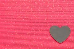 Μια μαύρη καρδιά που επιδεικνύεται σε ένα κόκκινο κυματιστό υπόβαθρο Στοκ εικόνα με δικαίωμα ελεύθερης χρήσης