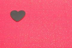 Μια μαύρη καρδιά που επιδεικνύεται σε ένα κόκκινο bakground Στοκ Εικόνες