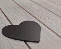 Μια μαύρη καρδιά σε έναν ξύλινο πίνακα Στοκ φωτογραφία με δικαίωμα ελεύθερης χρήσης