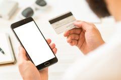 Μια μαύρη χλεύη smartphone επάνω και μια πιστωτική κάρτα στον επιχειρηματία χεριών Σε απευθείας σύνδεση πλαστική κάρτα πληρωμών ο Στοκ εικόνα με δικαίωμα ελεύθερης χρήσης