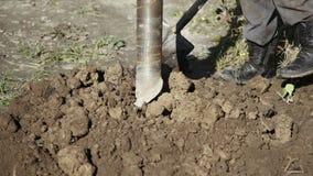 Μια μεγάλη βιομηχανική βίδα τρυπανιών εισάγει βαθμιαία το έδαφος φιλμ μικρού μήκους