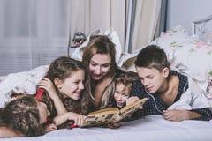 Μια μεγάλη ευτυχής οικογένεια Το Mom διαβάζει ένα βιβλίο στα παιδιά τους στο κρεβάτι Στοκ Εικόνα