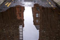 Μια μεγάλη λακκούβα στο δρόμο με την αντανάκλαση Μάντσεστερ στοκ εικόνες