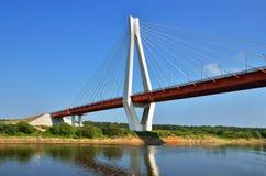Μια μεγάλη κόκκινη και άσπρη γέφυρα μέσω του ποταμού Στοκ φωτογραφία με δικαίωμα ελεύθερης χρήσης