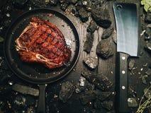 Μια μεγάλη ψημένη μπριζόλα βρίσκεται σε ένα σκοτεινό τηγανίζοντας τηγάνι Στοκ φωτογραφία με δικαίωμα ελεύθερης χρήσης