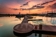Μια μεγαλοπρεπής ανατολή με τη βάρκα που στηρίζεται κοντά στην αποβάθρα ως foregrou στοκ εικόνες