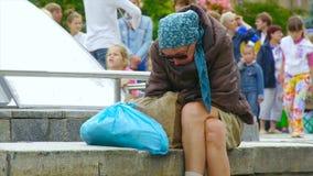 Μια μεθυσμένη άστεγη γυναίκα κάθεται στην οδό, που κατσαρώνουν επάνω απόθεμα βίντεο
