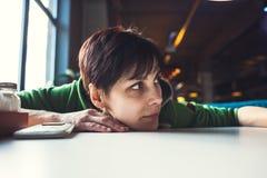 Μια μεθυσμένη γυναίκα κάθεται σε έναν πίνακα Στοκ Εικόνα