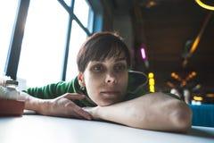 Μια μεθυσμένη γυναίκα κάθεται σε έναν πίνακα Στοκ φωτογραφίες με δικαίωμα ελεύθερης χρήσης