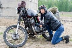 Μια μετα αποκαλυπτική γυναίκα κοντά στη μοτοσικλέτα κοντά στο κτήριο Στοκ Φωτογραφία