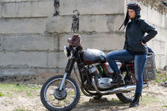 Μια μετα αποκαλυπτική γυναίκα κοντά στη μοτοσικλέτα κοντά στο κτήριο Στοκ Εικόνα