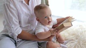 Μια μητέρα διαβάζει ένα βιβλίο στο νεογέννητο παιδί της, κάθονται στο πάτωμα στο χνουδωτό κάλυμμα απόθεμα βίντεο