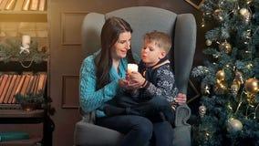Μια μητέρα και ένας γιος που έχουν τη διασκέδαση μπροστά από fir-tree με το κερί διακοπές δώρων Παραμονής Χριστουγέννων πολλές δι φιλμ μικρού μήκους