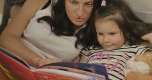 Μια μητέρα που διαβάζει στην κόρη της ένα βιβλίο πριν από το κρεβάτι απόθεμα βίντεο