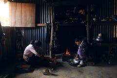 Μια μητέρα Tangkhul και η κόρη της που προετοιμάζουν το μεσημεριανό γεύμα το πρωί εκτός από την εστία στοκ εικόνα