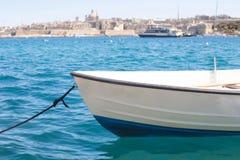 Μια μικρή βάρκα στη θάλασσα με μια καταπληκτική πανοραμική άποψη μιας αρχαίας πρωτεύουσας Valletta στη Μάλτα στο υπόβαθρο Στοκ Εικόνες