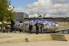 Μια μικρή ομάδα τουριστών κουβεντιάζει μαζί και συγκρίνει τις σημειώσεις εκτός από το σολομό του γλυπτού Μπέλφαστ ψαριών γνώσης Στοκ Εικόνα