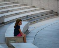 Μια μικρή συνεδρίαση κοριτσιών στα σκαλοπάτια στον κόλπο μαρινών Στοκ Φωτογραφία