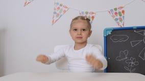 Μια μικρή συνεδρίαση κοριτσιών στον πίνακα στο βρεφικό σταθμό που χτυπά τα χέρια του στον πίνακα φιλμ μικρού μήκους
