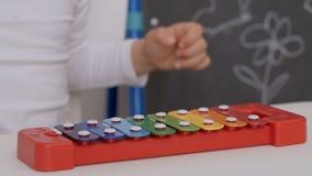 Μια μικρή συνεδρίαση κοριτσιών στον πίνακα στο δωμάτιο των παιδιών που παίζει το xylophone φιλμ μικρού μήκους