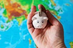 Μια μικροσκοπική piggy τράπεζα κρατιέται στο χέρι Ένας ζωηρόχρωμος χάρτης του wor στοκ εικόνα