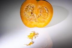 Μια μισή πορτοκαλιά κολοκύθα με τους σπόρους στο άσπρο υπόβαθρο στοκ εικόνες