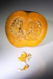 Μια μισή πορτοκαλιά κολοκύθα με τους σπόρους στο άσπρο υπόβαθρο στοκ φωτογραφίες
