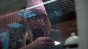 Μια μοντέρνη γυναίκα hipster στα γυαλιά που χρησιμοποιούν app στο smartphone σε έναν καφέ Όψη μέσω του παραθύρου απόθεμα βίντεο