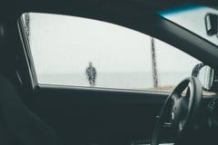 Μια μουτζουρωμένη σκιαγραφία ενός ανθρώπου που βλέπει μέσω του υγρού παραθύρου αυτοκινήτων στοκ εικόνα