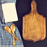 Μια μπλε πετσέτα κουζινών και ένα σημειωματάριο σε ένα σκοτεινό ξύλινο υπόβαθρο Επιλογές, θέση για το κείμενο, συνταγή Στοκ φωτογραφία με δικαίωμα ελεύθερης χρήσης