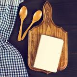 Μια μπλε πετσέτα κουζινών και ένα σημειωματάριο σε ένα σκοτεινό ξύλινο υπόβαθρο Επιλογές, θέση για το κείμενο, συνταγή Στοκ εικόνες με δικαίωμα ελεύθερης χρήσης