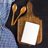 Μια μπλε πετσέτα κουζινών και ένα σημειωματάριο σε ένα σκοτεινό ξύλινο υπόβαθρο Επιλογές, θέση για το κείμενο, συνταγή Στοκ φωτογραφίες με δικαίωμα ελεύθερης χρήσης
