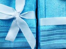Μια μπλε πετσέτα που δεσμεύεται από ένα μπλε υπόβαθρο τόξων kaak για τίποτα Παρόν για τις γυναίκες στοκ εικόνες