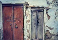 Μια μπροστινή άποψη του παλαιού εκλεκτής ποιότητας ξύλου χάρασε τις κλειστές πόρτες ενός παλαιού σπιτιού με το ραγισμένο τοίχο στ στοκ εικόνα με δικαίωμα ελεύθερης χρήσης