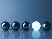 Μια μπλε καμμένος ελαφριά σφαίρα που ξεχωρίζει από τις σφαίρες σφαιρών μετάλλων στο σκούρο μπλε υπόβαθρο ελεύθερη απεικόνιση δικαιώματος