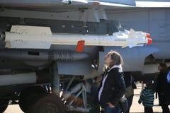Μια νέα έγκυος γυναίκα εξετάζει ένα βλήμα που τοποθετείται σε έναν οδηγό κάτω από το φτερό ενός αεροσκάφους αγώνα Στοκ Εικόνες